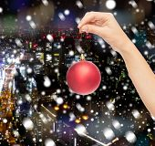 christmas, decoration, holidays and people concept - close up of woman hand holding christmas ball over snowy night city background