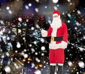 christmas, holidays, gesture and people concept- man in costume of santa claus showing thumbs up over snowy night city background