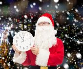 christmas, holidays and people concept - man in costume of santa claus with clock showing twelve over snowy night city background