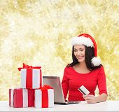christmas, shopping and people concept - smiling woman in santa helper hat with gift boxes, laptop computer and credit card over yellow lights background