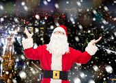 christmas, holidays and people concept - man in costume of santa claus with raised hands over snowy night city background