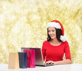 christmas, holidays, technology and people concept - smiling woman in santa helper hat with shopping bags and laptop computer over yellow lights background