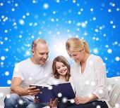 family, christmas, holidays and people - smiling mother, father and little girl reading book over blue snowy background