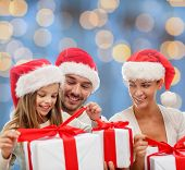 family, christmas, generation, holidays and people concept - happy family in santa helper hats with gift boxes over blue lights background