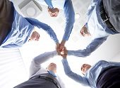 business, people and teamwork concept - smiling group of businesspeople standing in circle and making high five gesture