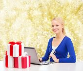 christmas, holidays, technology and shopping concept - smiling woman with gift boxes, credit card and laptop computer over yellow lights background
