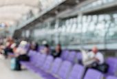 Blurred Image Of A Man Read Newspaper While Waiting The Flight In Departure Lounge Of Airport.