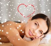beauty, health, holidays, people and spa concept - beautiful woman in spa salon getting hot stones massage over snowflakes with red heart shape background