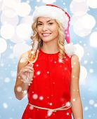 party, drinks celebration and people concept - smiling woman in santa helper hat and red dress with glass of champagne over blue lights background