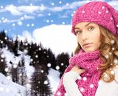 happiness, winter holidays, christmas and people concept - young woman in pink hat and scarf over snowy mountains background