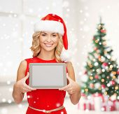 holidays, technology and people concept - smiling woman in santa helper hat showing tablet pc computer blank screen over living room and christmas tree background