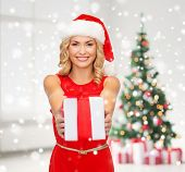 holidays, celebration and people concept - smiling woman in santa helper hat and red dress with gift box over living room and christmas tree background