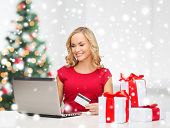 technology, holidays, online shopping and people concept - woman with credit card, gift boxes and laptop computer over living room background