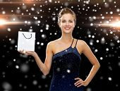 luxury, advertisement, christmas, holidays and sale concept - smiling woman with white blank shopping bag over night lights and snow background