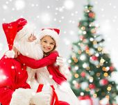 holidays, christmas, happiness and people concept - smiling girl with gift box embracing santa claus at home