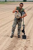 Kiev,Ukraine.June 3.Military archeology. Man with metal detector and German WWII anti tank landmine.At June 3,2012 in Kiev, Ukraine