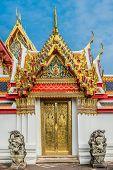 golden door and dragon statues at Wat Pho temple Bangkok Thailand