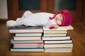 baby sleeping on stack of books