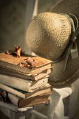 Straw Hat And Old Books On Chair