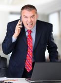 Angry businessman screaming into the mobile phone