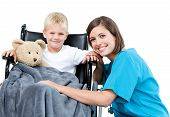 picture of teddy-bear  - Nice female doctor carrying adorable little boy with his teddy bear in the wheelchair at the hospital - JPG
