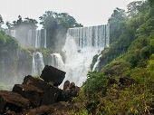 Iguazu Falls Framed By Rocks And Foliage