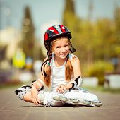 Little girl in roller skates sitting on a city street