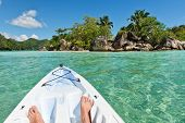 Exploring the Port Launay Marine National Park, Seychelles in a canoe or kayak with a view of the kayakers bare feet in the prow