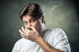 picture of disgusting  - Man with disgusted expression closing his nostrils with his fingers - JPG