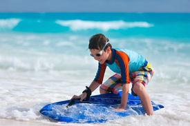 stock photo of boogie board  - Little boy on vacation having fun surfing on boogie board - JPG