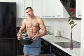 picture of pinafore  - Man with big muscles in an apron with a pan in hand stands in the kitchen - JPG