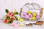 stock photo of easter basket eggs  - Easter composition with Easter eggs in basket and flowers - JPG