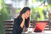 picture of handphone  - A portrait of a Young businesswoman work oudoor in a cafe - JPG