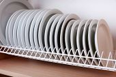 stock photo of racks  - Clean plates drying on metal dish rack on shelf - JPG