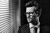 foto of jalousie  - Serious young businessman in eyeglasses looking through jalousie - JPG