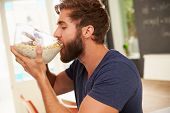 stock photo of table manners  - Hungry Young Man Eating Breakfast From Glass Bowl - JPG