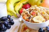 pic of cereal bowl  - Bowl of cereal with fruit on a white wooden table and fresh fruits behind - JPG