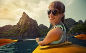 picture of kayak  - Smiling lady sitting in the kayak with limestone mountains of the Ha Long Bay  - JPG