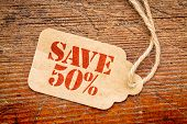 picture of 50s  - save 50 percent  sign a paper price tag against rustic red painted barn wood  - JPG