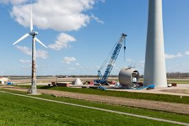 pic of enormous  - Dutch farmland with replacement of old wind tubines through enormous new wind turbines - JPG