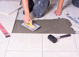 picture of ceramic tile  - Tiler installing ceramic tiles on a floor - JPG