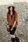 Постер, плакат: Beautiful Stylish Boho Woman Hipster With Hat Leather Bag Fringe Poncho And Boots Girl In Gypsy H
