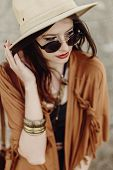 Постер, плакат: Beautiful Stylish Boho Woman In Sunglasses And Hat Fringe Poncho And Leather Bag Hipster Girl In G