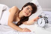 Woman in bed reach for alarm clock