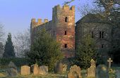 Ruins of Acton Burnell fortified house in Shropshire, gravestones to foreground