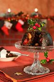 Christmas pudding decorated with holly and berries in festive setting with fireplace in background