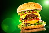 stock photo of beef-burger  - Tasty hamburger and french fries on a dark background - JPG