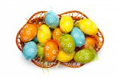 color easter eggs in basket isolated on white. top view