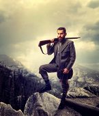 Bearded old-fashioned hunter in rocky mountain poster