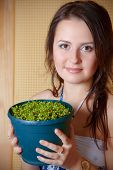 Young beautiful woman with small plant in flowerpot